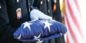 White gloved hands hold a folded American flag.