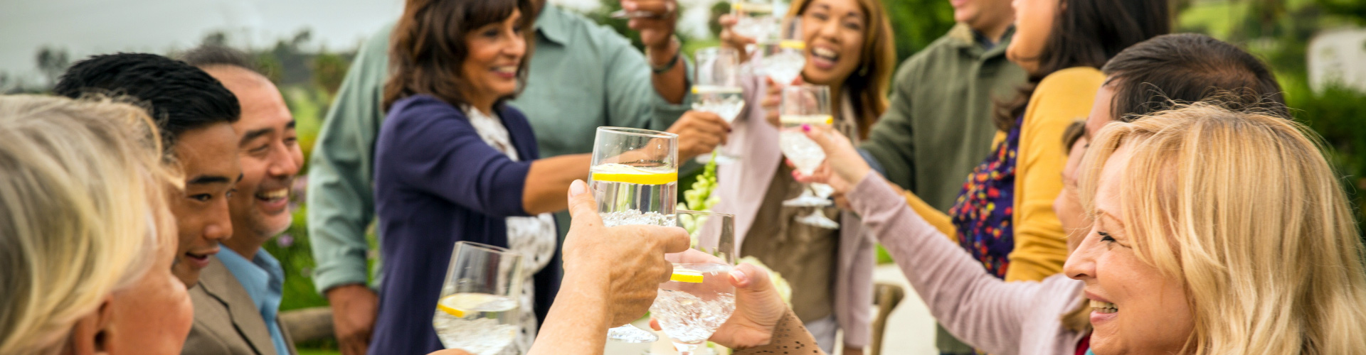 A group of people raise their glasses to toast to a loved one at an outdoor celebration.