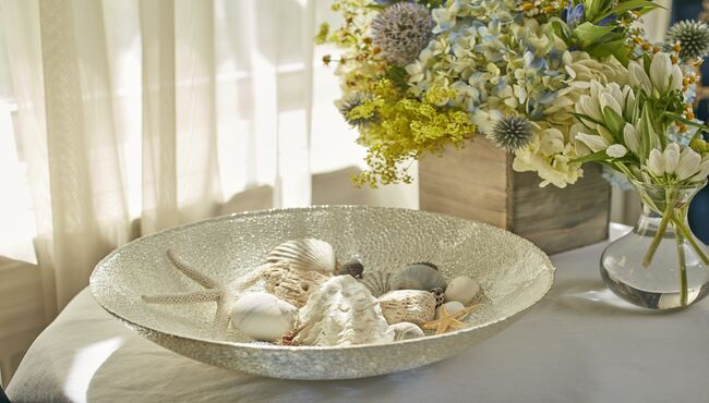 Shells in a glass bowl near a flower arrangement for a beach-themed life celebration.