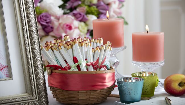 Personalized take-away pencils in a basket in a memorial display.