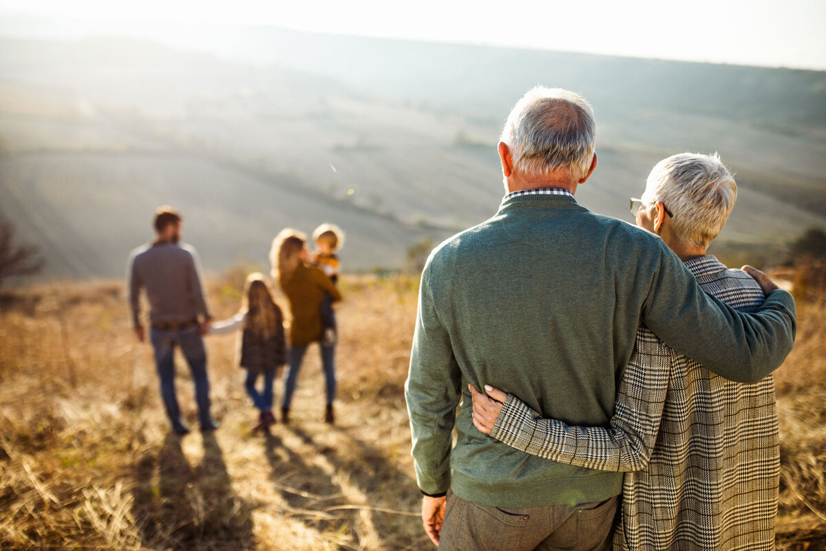 Senior couple embracing and looking over rest of family