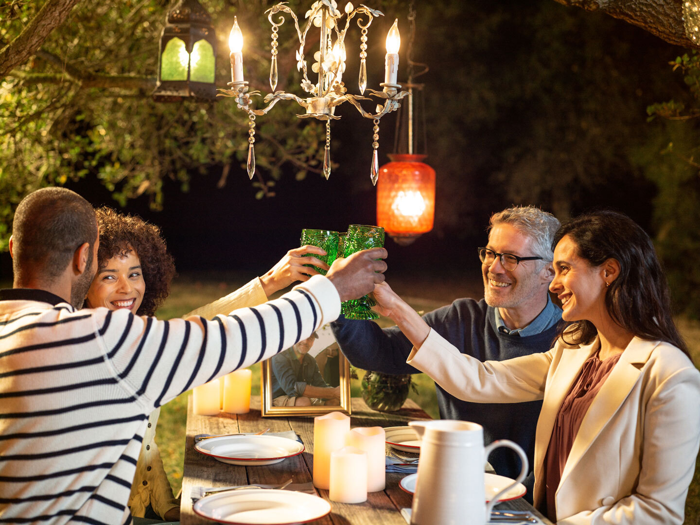people toasting in celebration of remembrance at a picnic table outdoors at night