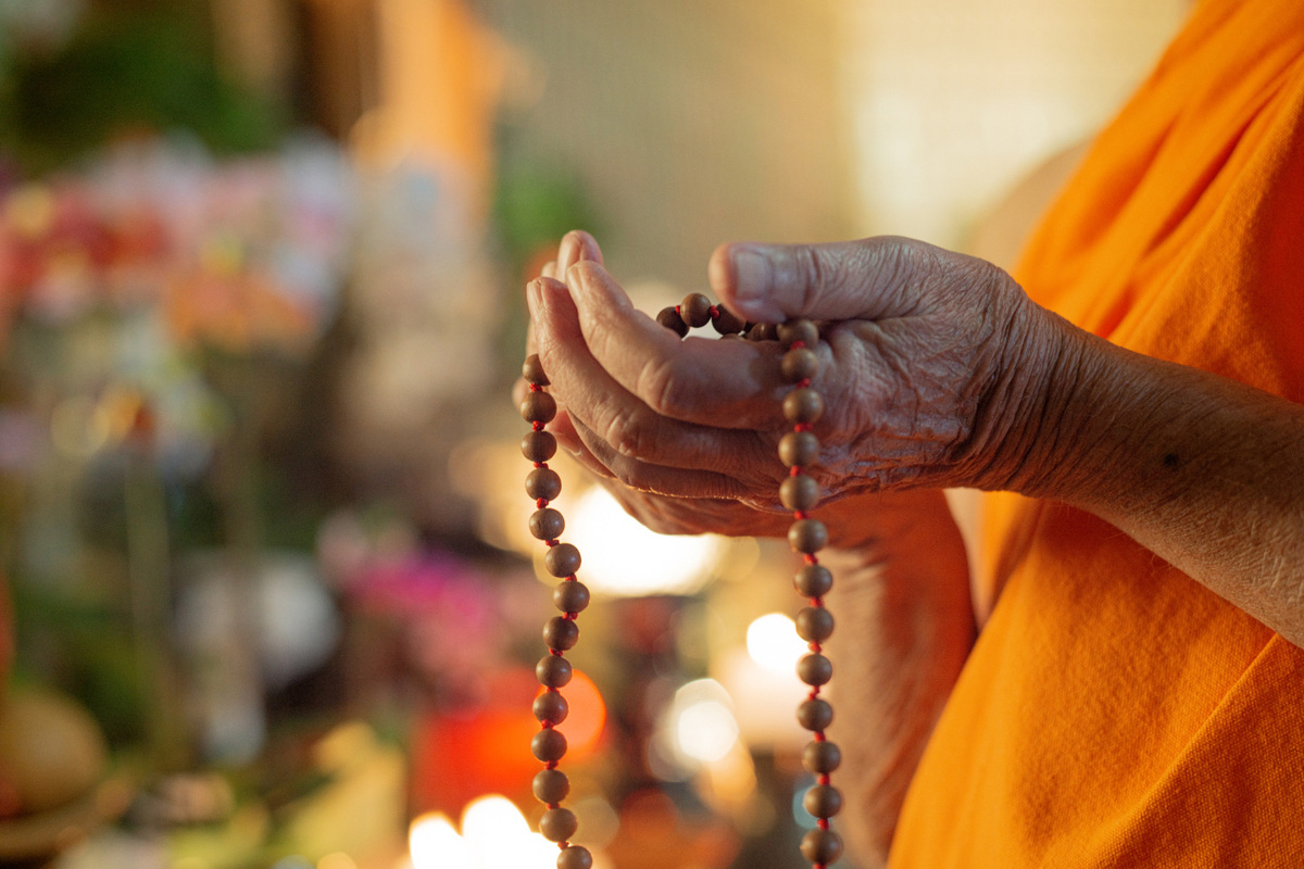 Buddhist monk's hands holding prayer beads