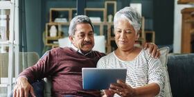 senior couple looking at tablet on couch