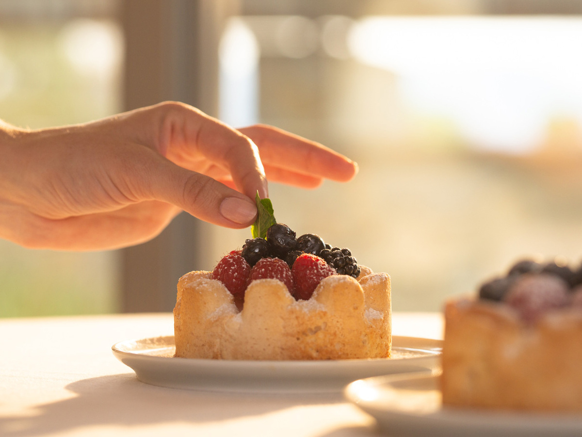 close up of hand placing garnish on dessert