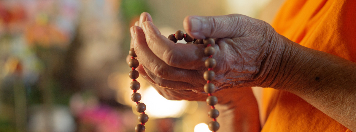 hands holding prayer beads