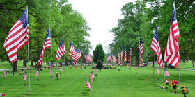 Row of American flags leading to a water fountain at Resthaven Cemetery